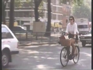 Woman cycling around Shepherds Bush Green - lovely practical bike!