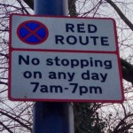 a typical red route sign, in this case showing a no topping 7AM-7PM restriction every day on the South Circular in Forest Hill